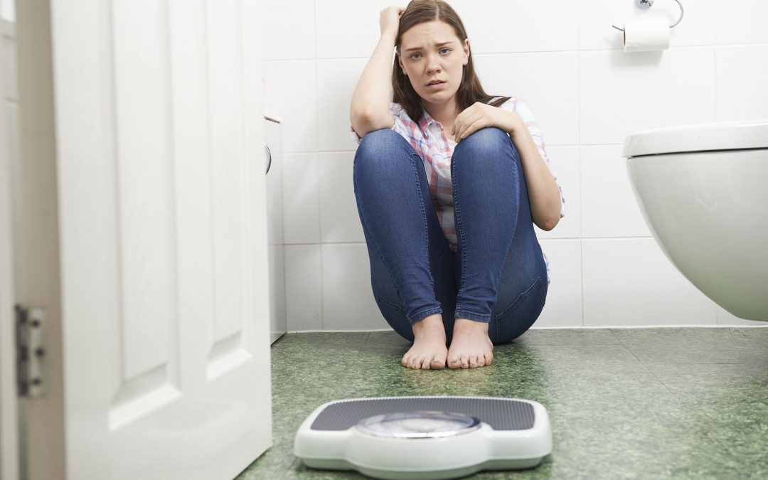 Unhappy Teenage Girl Sitting On Floor Looking At Bathroom Scales